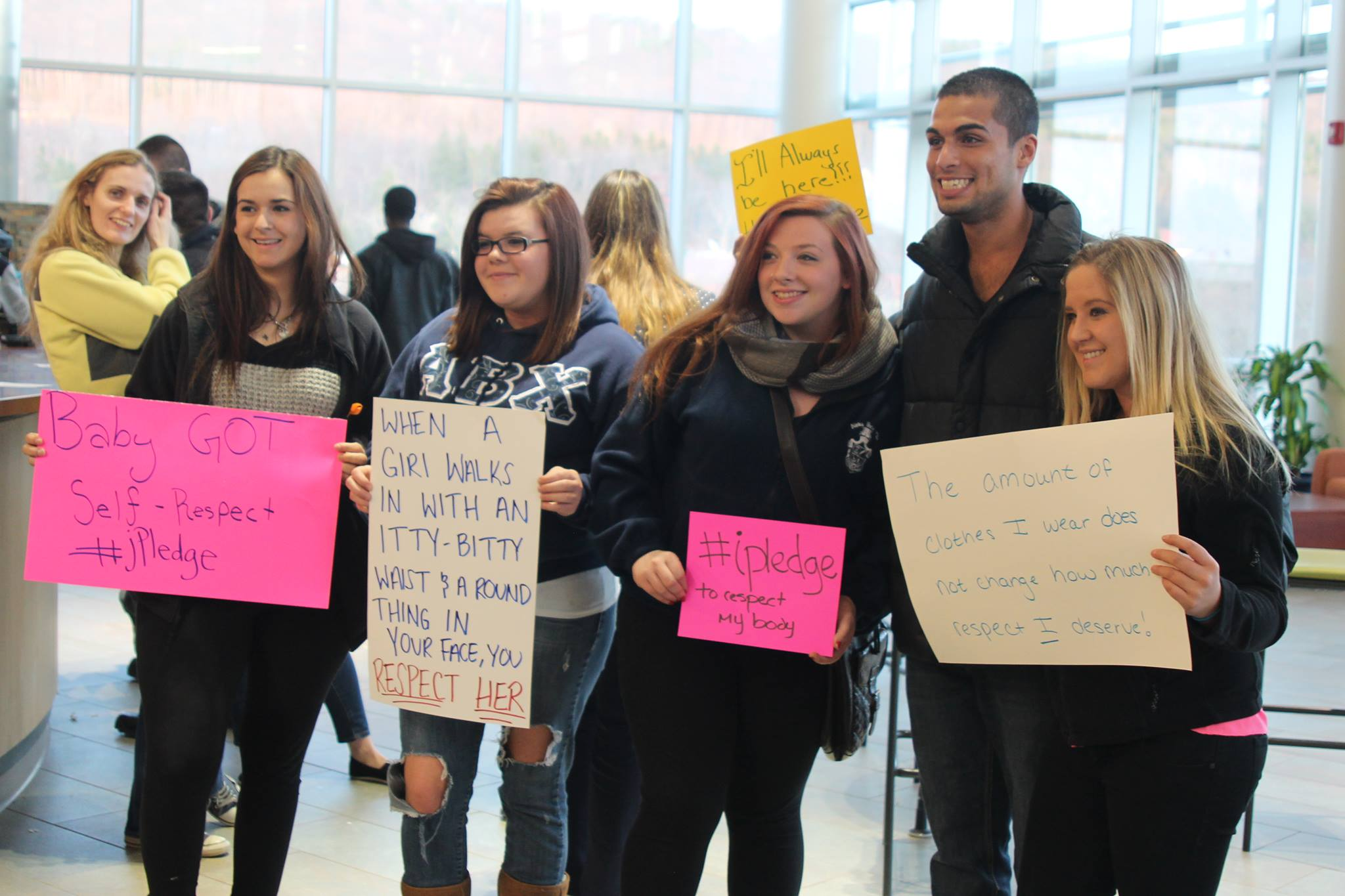 students at Take Back The Night event holding posters