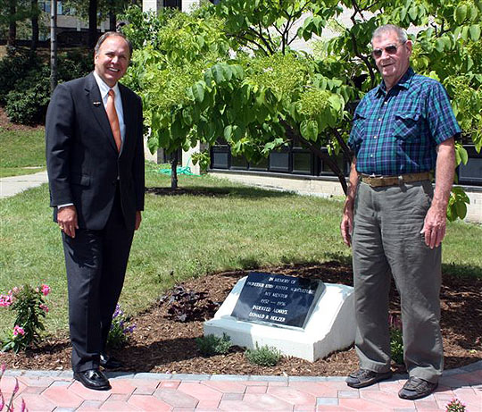 President Anderson and Donald Holzer stand near the garden.