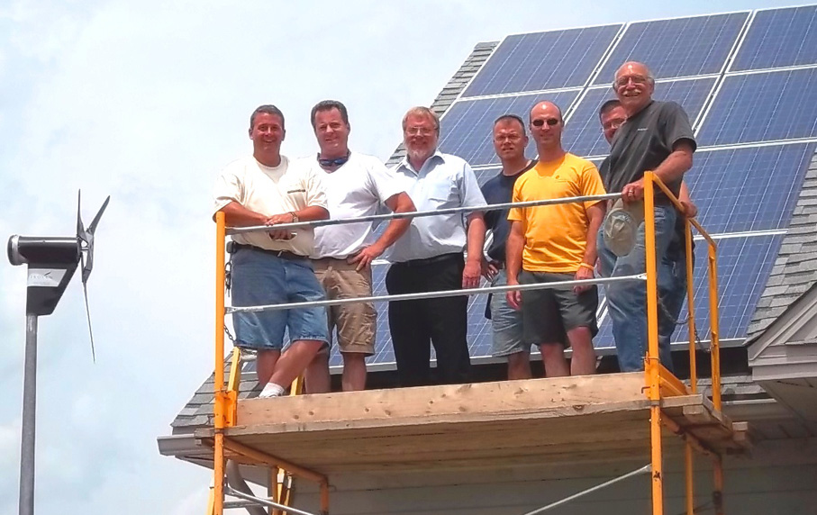 Workshop instructors and participants on scaffolding in front of solar panel with wind turbine to the left of them.