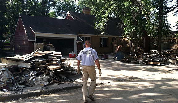 Officer Bingham in front of a house destroyed by the flood.