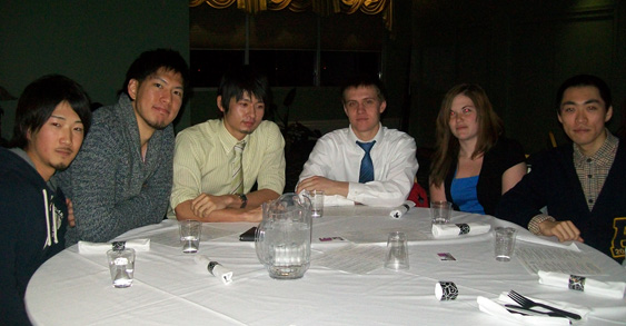 Students sitting around a table at bi-annual international dinner