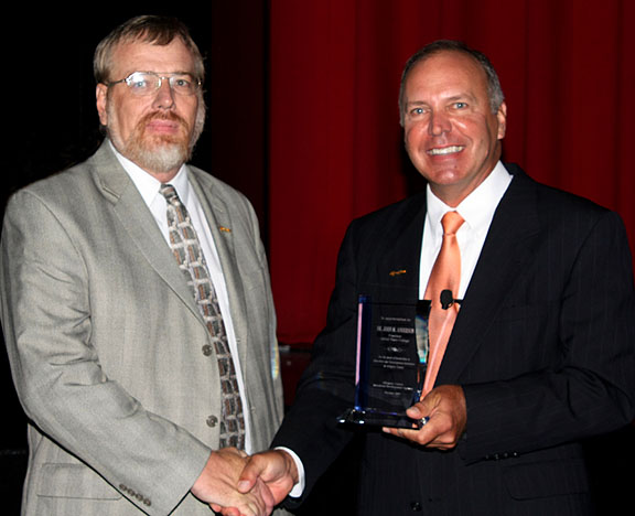 Clark (left) accepts the award from Anderson