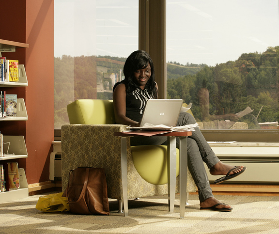 female student sitting in a chair in the library