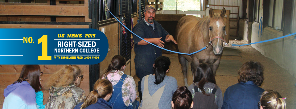 No. 1 Right-Sized Norther College with Enrollment from 2,000-5,000 US News 2019. Image of vet tech students large animal class in the horse barn.