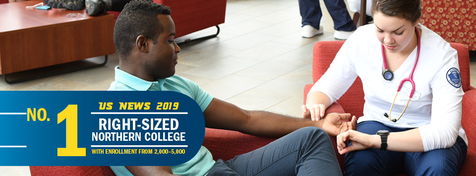 No. 1 Right-Sized Norther College with Enrollment from 2,000-5,000 US News 2019. Image of nursing student taking another student's blood pressure.