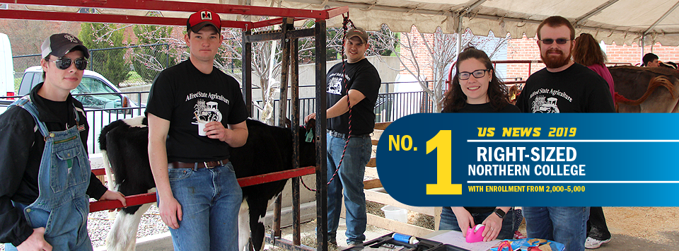No. 1 Right-Sized Norther College with Enrollment from 2,000-5,000 US News 2019. Image of Ag students wearing matching shirts and cows in the background.
