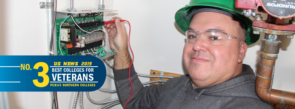 US News 2019 No. 3 Best Colleges for Veterans, public northern colleges. Image of adult HVAC student in green hard had by pipes and control unit