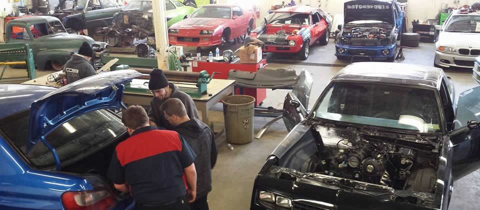 students looking under the hood of a car in automotive lab