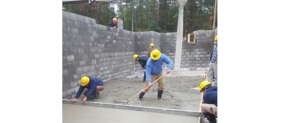 students working on basement of a house