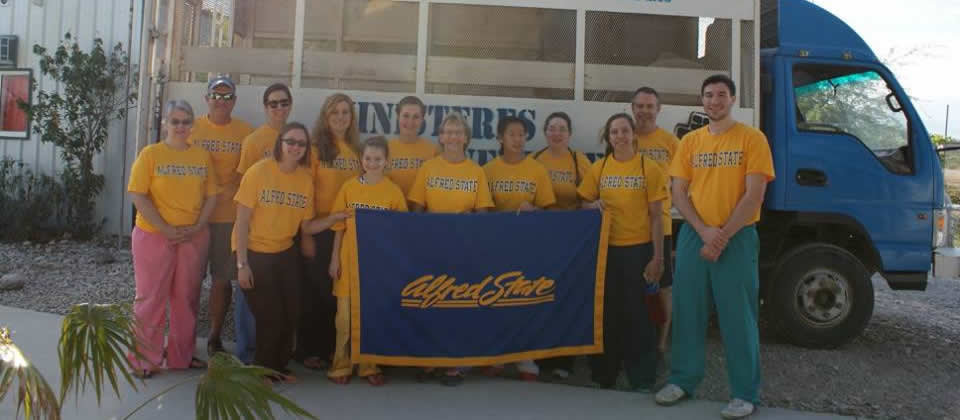 several people wearing yellow shirts that say Alfred State, holding a blue Alfred State banner