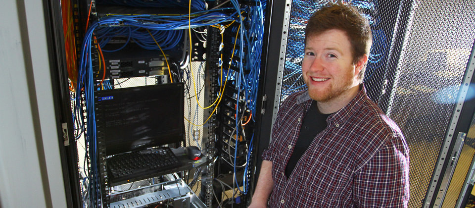 male student standing in front of a box of wires