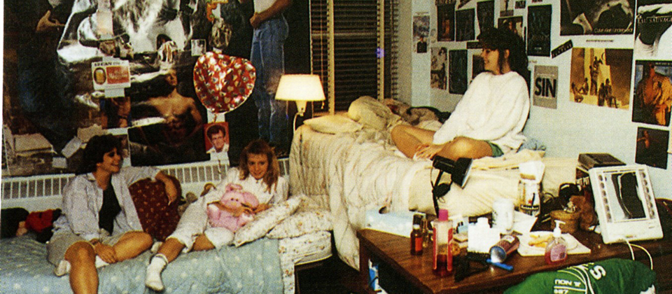 three girls sitting on beds in a dorm room