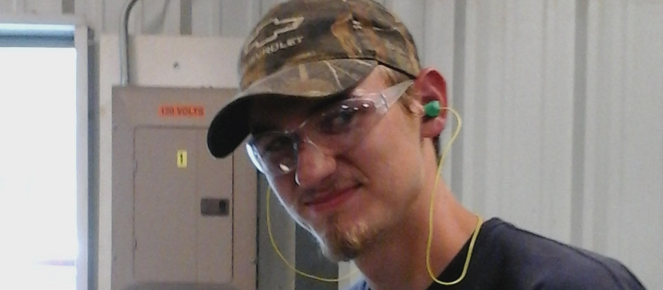 male student wearing safety glasses, a hat, and ear plugs