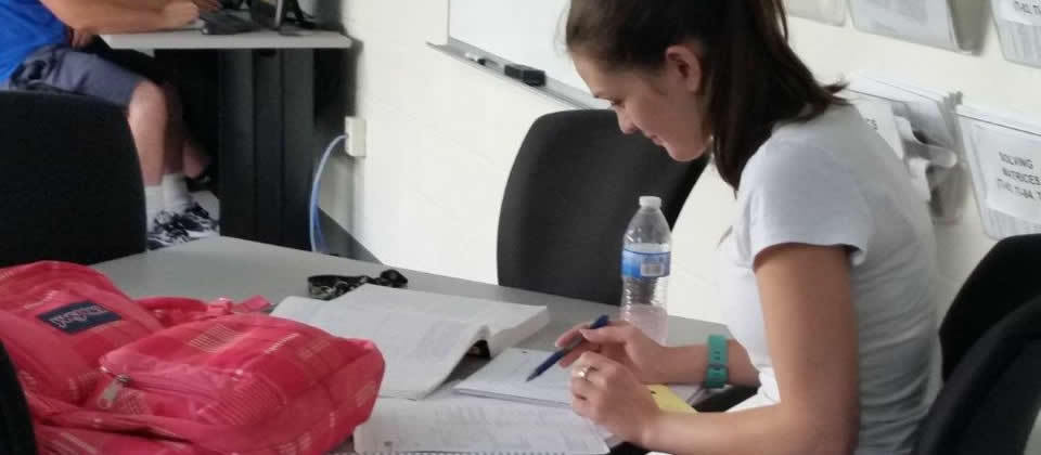 female student at a desk with backpack