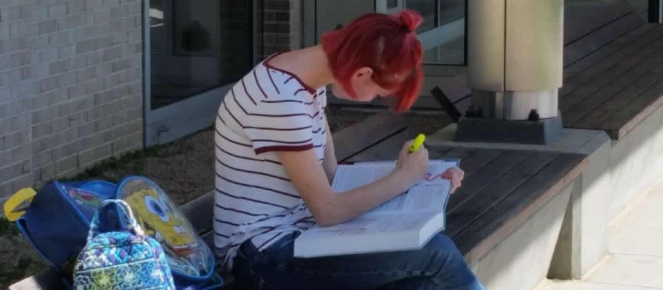 female student reading book sitting on a bench