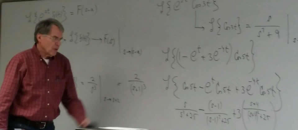professor in front of white board with writing