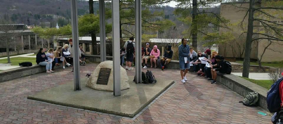 students sitting down in front of the bell tower