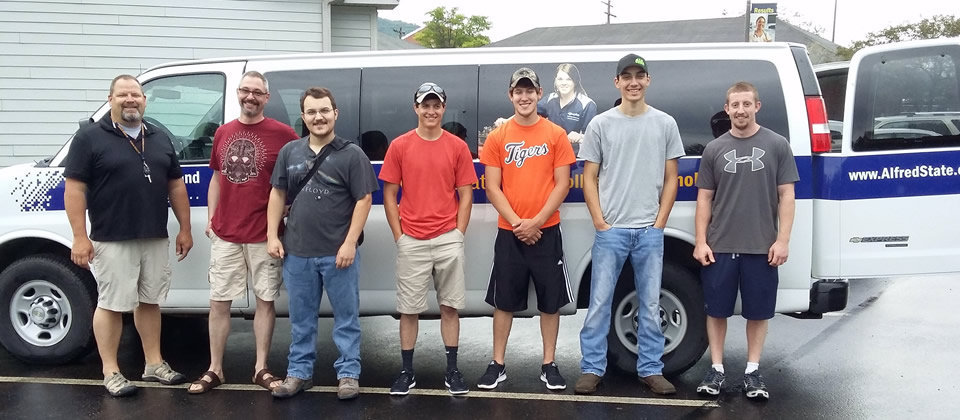 students standing in front of a van