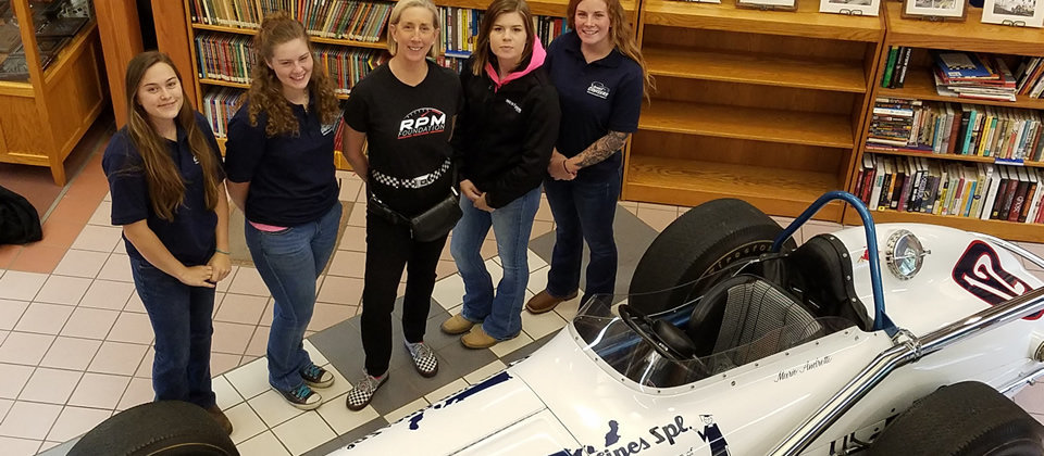 four female students standing with a female race driver