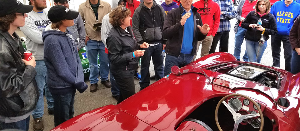 students standing around a red race car