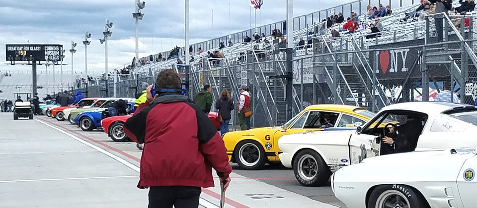 person in red coat and line of classic cars