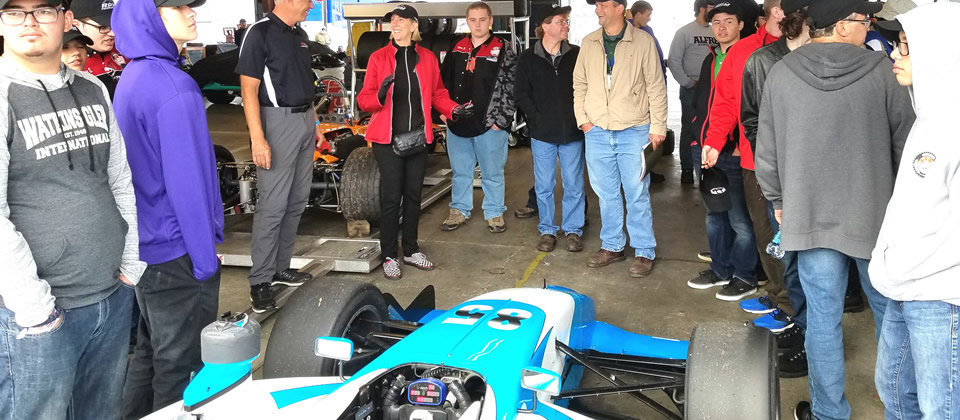 students standing around a race car