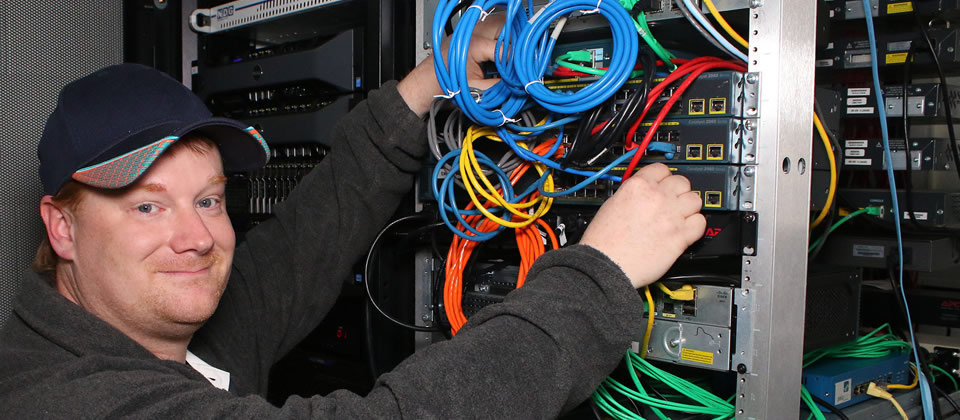 male student holding a bunch of different colored wires
