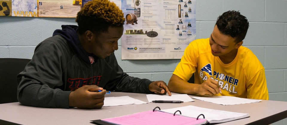 two male students sitting at a table looking at a paper