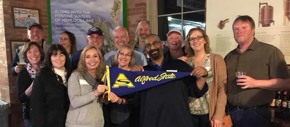 group of alumni holding and Alfred State banner