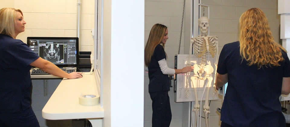 three female students with skeleton and x-ray machine