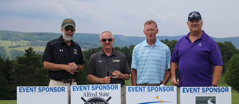 four golfers standing on a course, in front of some yard signs that list sponsor information