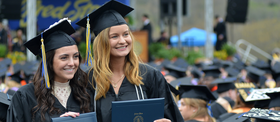 two female students wearing a cap and gown holding diplomas