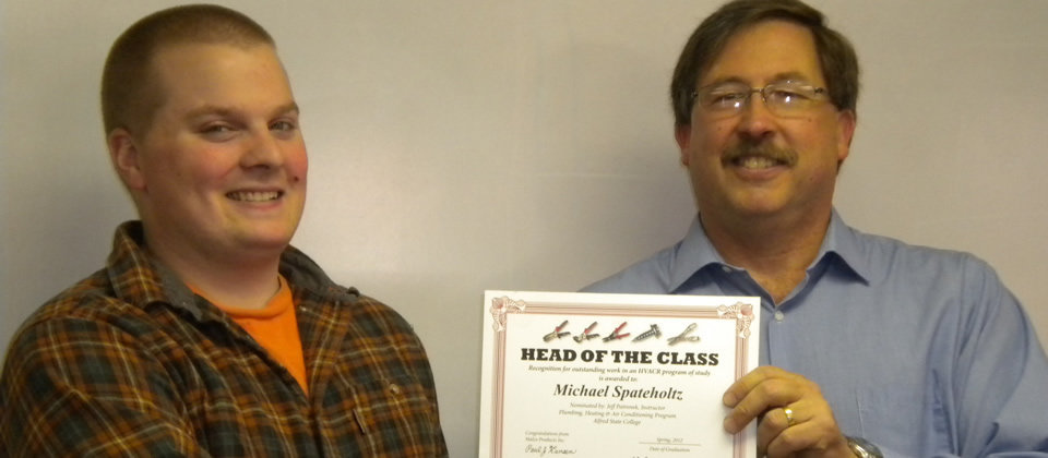 instructor with student holding a certificate that says 'head of the class'