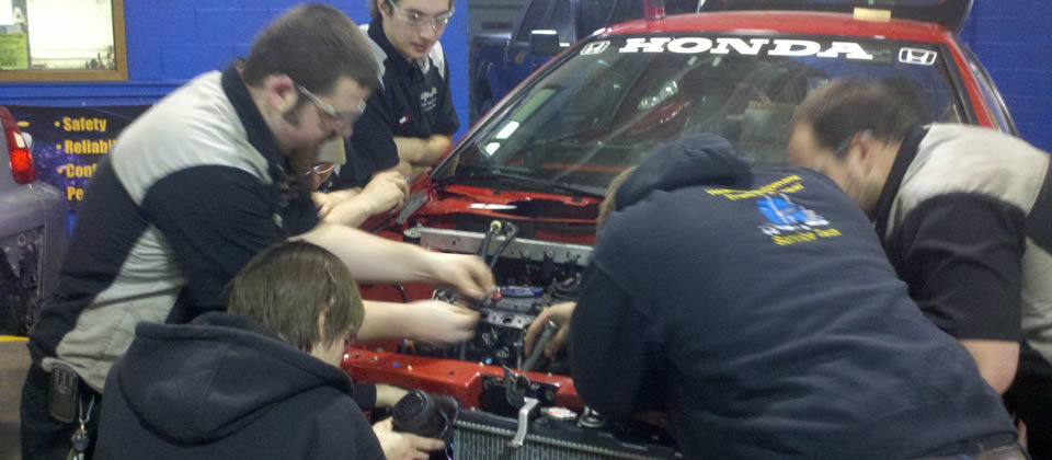 students working on a car in auto lab