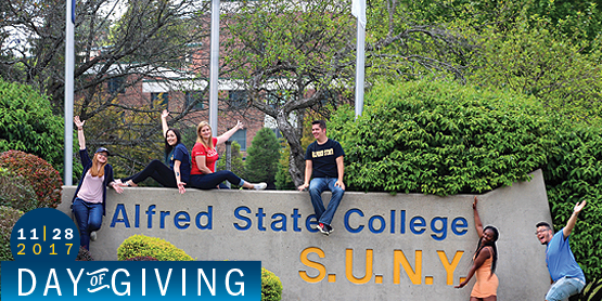 students sitting on a stone at front entrance of the college, Alfred State SUNY, 11-28-17, Day of Giving
