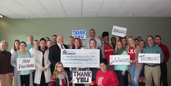Students, faculty, and staff present a check and hold up thank you signs