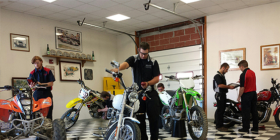 students in a classroom next to motorcycles