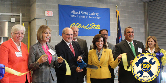 Photo of ribbon being cut. Front row from left, College Council Chair Pat Fogarty, State Sen. Catharine Young, President Dr. Skip Sullivan, Lt. Gov. Kathy Hochul, Assemblyman Joe Giglio, and Educational Foundation President Julie Hart; and, back row, from left, V.P. Craig Clark and Allegany County Board of Legislators Chair Curt Crandall.