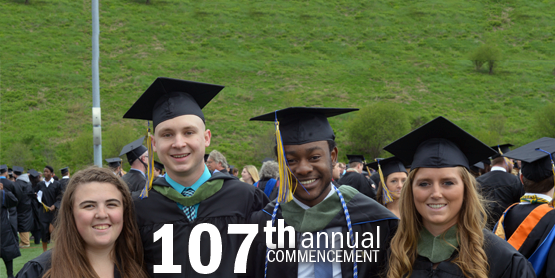 107th annual commencement, students wearing their cap and gown outside