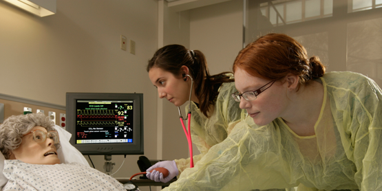 two nursing students in a lab setting