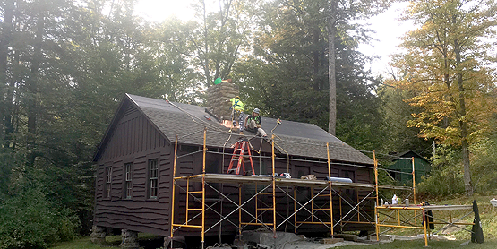 brown 2-story cabin, scaffolding, students on the roof