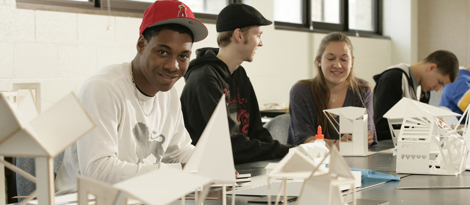students in a classroom with some models on the table in front of them