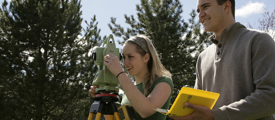 female and male student using surveying equipment outside