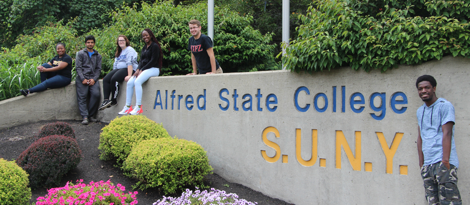 students standing next to stone at main entrance to campus