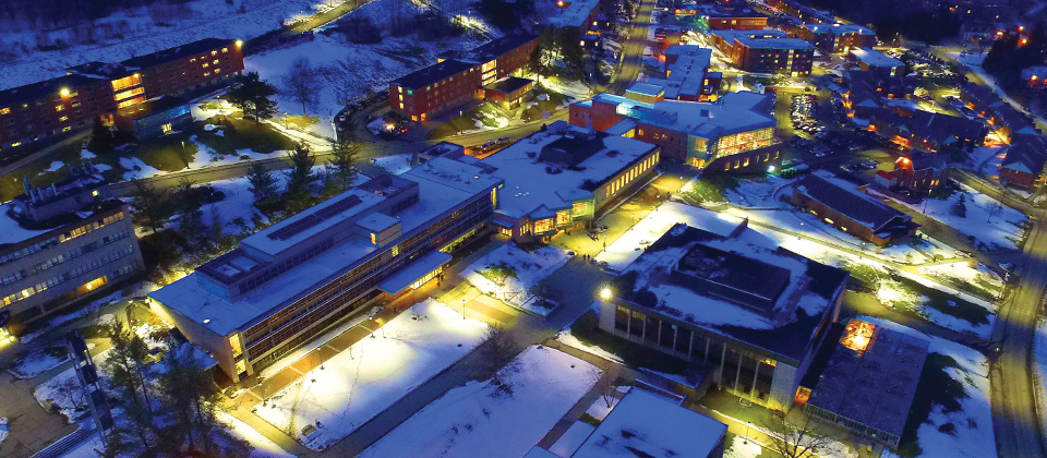 buildings on campus at night covered in snow