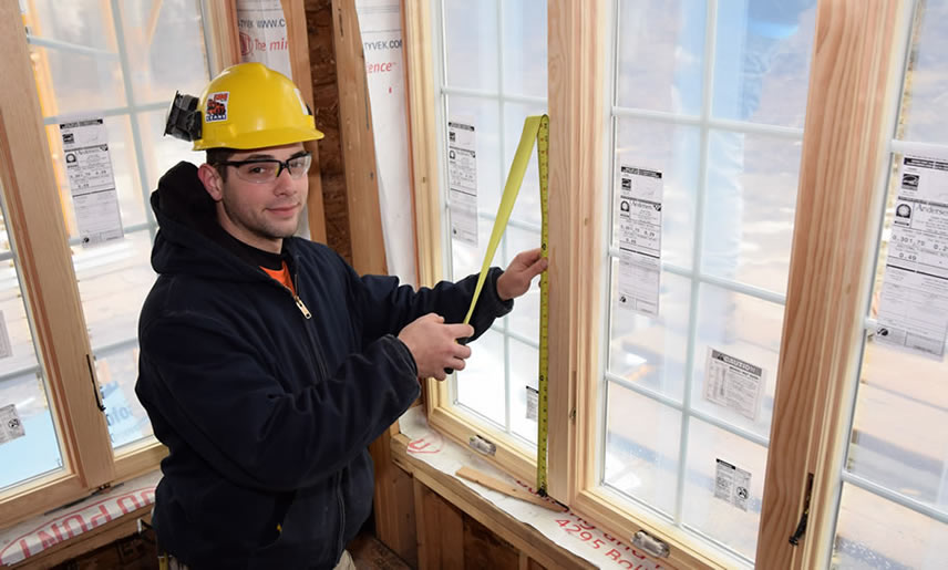 Aaron Aumick holding a ruler next to a window