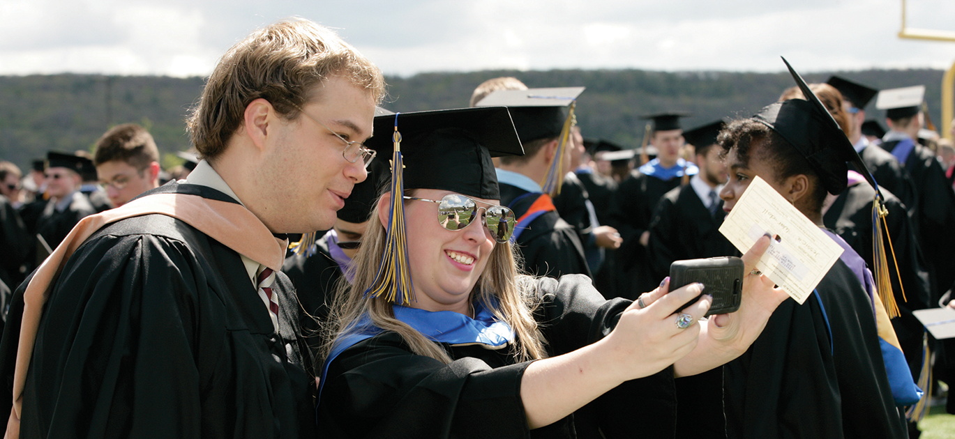 male and female student taking a selfie at commencement