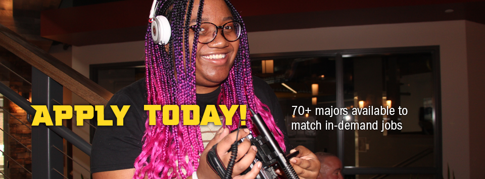 Apply Today! 70+ majors available to match in-demand jobs. Image of digital media student with headphones and pink hair holding video camera.