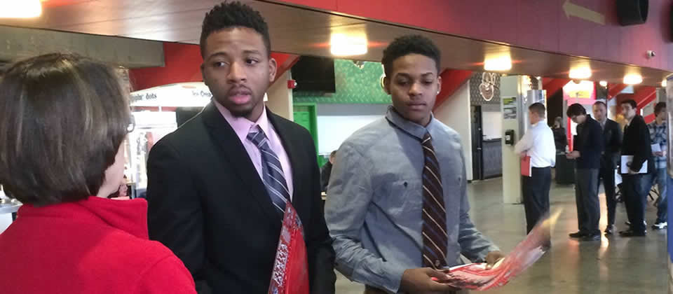 two male students speaking with an employer at a career fair