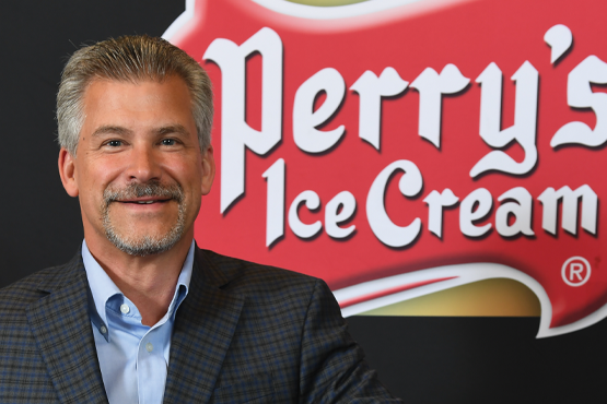 Brian Perry standing in front of Perry's Ice Cream logo
